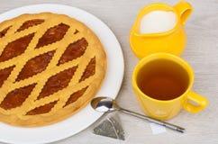 Shortbread pie, tea, jug milk and tea pack on table Stock Image