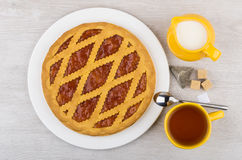 Shortbread pie, tea, jug milk and tea pack on table Royalty Free Stock Photography