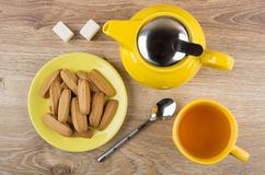 Shortbread in saucer, teapot, sugar and cup of tea Royalty Free Stock Images