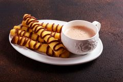 Shortbread sticks with chocolate drizzle. And cup of cappuccino Royalty Free Stock Photos