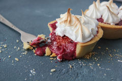 Shortbread tart with raspberry curd and meringue. Sand tarts with raspberry curd, chili and merengue on a concrete background Stock Photography