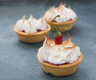 Shortbread tart with raspberry curd and meringue. Sand tarts with raspberry curd, chili and merengue on a concrete background Royalty Free Stock Images