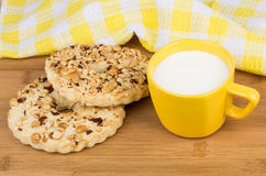 Shortbreads rings with peanuts and cup of milk on table Royalty Free Stock Image