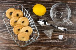 Shortbreads in transparent bowl, cup, teabag, spoon and lemon Royalty Free Stock Photography