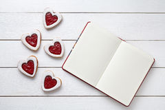 Shortbred heart shaped cookies with empty notebook frame, composition on white wooden background for Valentines day. Royalty Free Stock Photo