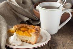 Shortcrust brzoskwini kulebiak, beza i filiżanka herbata, Zdjęcia Royalty Free