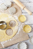 Shortcrust pastry making little tart on molds on rustic background with rolling pin and flour on table Stock Photo