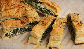 Shortcrust pastry roll stuffed with spinach and ricotta cheese. Slices of shortcrust pastry roll stuffed with spinach and ricotta cheese on papel Stock Images