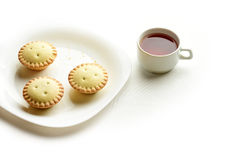 Shortcrust tartlets on a plate with cup of tea Stock Photography
