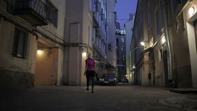 Shortcut blondie woman goes out from inner yand to the street at dark night stock footage
