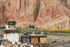 Shortens, yellow trees and red cliff in Dahkmar village, Mustang. Buddhist shorten at foot of the Dahkmar village red cliff in Mustang, Nepal, Himalaya . Poplars Stock Photos