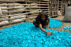 Shorting Plastic. A woman is spreading plastic bottle caps on the floor in the slum area of India Royalty Free Stock Photos