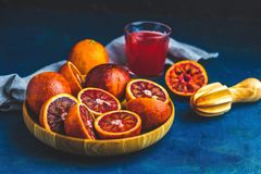 Shorts of alcohol cocktail with Sliced Sicilian Blood oranges and fresh red orange juice. Served on dark blue concrete table surface. Dark rustic style royalty free stock photography