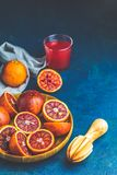 Shorts of alcohol cocktail with Sliced Sicilian Blood oranges and fresh red orange juice. Served on dark blue concrete table surface. Dark rustic style royalty free stock image