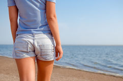 Shorts and beach. Girl with shorts stands back on the beach stock images