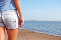 Shorts and beach. Girl with shorts stands back on the beach Royalty Free Stock Photography