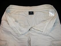 Shorts beige, front side unbuttoned, with labels, on black background. Image royalty free stock image