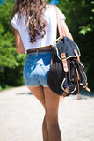 Shorts d'uso dei jeans della ragazza con la camminata dello zaino Immagine Stock Libera da Diritti