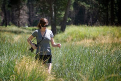 Shorts da mulher adulta e caminhadas vestindo do t-shirt através das madeiras Fotografia de Stock Royalty Free