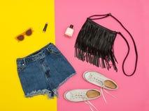 Shorts de denim, espadrilles blanches, sac à main et verres Fond lumineux concept à la mode Photos stock