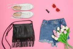 Shorts de denim, espadrilles blanches, sac à main noir et bouquet de tulipe Image stock