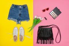 Shorts de denim, espadrilles blanches, sac à main noir et bouquet de tulipe Images libres de droits