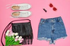 Shorts de denim, espadrilles blanches, sac à main noir et bouquet de tulipe Photo libre de droits