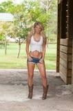 Shorts de port de blue-jean de femme dans ou autour d'une grange Photographie stock libre de droits