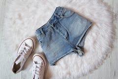 Shorts et espadrilles de denim sur la fourrure blanche concept à la mode Photographie stock