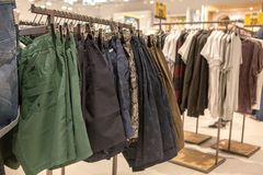 Shorts on the store shelf. Fashionable clothes on the shelves in the store. Shorts hanging on the vests in the fashion store. Showcase, sale, shopping royalty free stock image