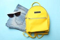 Shorts, stylish yellow backpack and sunglasses stock photo