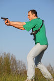 Shot. Man in green t-shirt with gun Stock Images