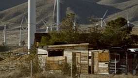 A shot of an abandond habitation. A videoshot of an abandond habitation located in the outskirts with windmills and mountains on the background stock footage
