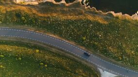 Aerial shot from above driving black car in a field by the rural road near a cliff at the seaside. In summer at sunset stock video footage