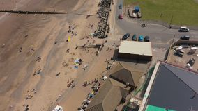 4K Aerial footage looking down at families on sandy Hornsea Beach