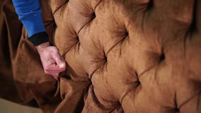 Man makes a design for a couch. Shot from above of a worker`s hand making a design for a new sofa. Sofa`s upholstery is brown velour stock footage