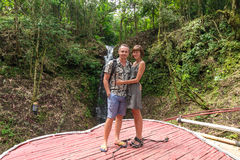 Shot of affectionate young honeymoon couple standing together in rainforest. Couple in love standing near a waterfall in Stock Photography
