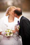 Shot of aged groom and bride kissing against river Royalty Free Stock Photography