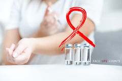 Shot with AIDS red sign of woman doing puncture with disposal syringe Royalty Free Stock Photos