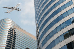 Shot of airplane flying above skyscrapers in City of Bangkok downtown Royalty Free Stock Images