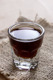 Shot of alcohol on wooden table Stock Image