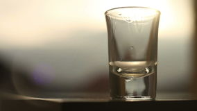 Shot of alcoholic beverage, residuary drops flowing down with sun flares stock footage