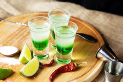Shot alcoholic cocktail. Mexican alcoholic drinks shot on a wooden board. Good tequila booze with decor composition and barman. Different layers of vodka Royalty Free Stock Image