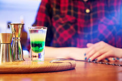 Shot alcoholic cocktail. Mexican alcoholic drinks shot on a wooden board. Good tequila booze with decor composition and barman. Different layers of vodka Royalty Free Stock Photo