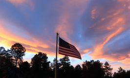 American Flag blowing in the wind at Sunset. A shot of the American Flag blowing in the wind with a beautiful sunset and silhouetted trees for a backdrop Royalty Free Stock Image