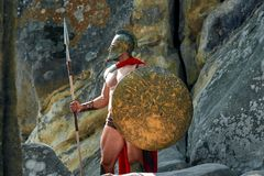Mature Spartan warrior in the woods. Shot of an armored medieval soldier wearing a helmet holding a spear and a shield standing outdoors looking away masculinity Stock Photos