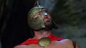 Medieval warrior in the woods. Shot of an armored medieval spartan wearing a helmet hiding behind his shield looking cautious while searching for his enemy in stock footage