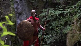 Medieval warrior in the woods. Shot of an armored spartan in a helmet and cape holding his shield standing alone in the forest looking around courage bravery stock video footage