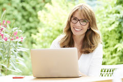 Woman with laptop. Shot of an attractive happy woman using her laptop while sitting in the garden at home Stock Photos