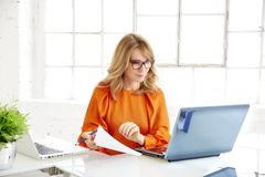 Shot of attractive mature businesswoman sitting at office desk behind her laptops and working royalty free stock images